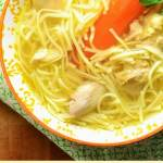 Chicken noodle soup with carrot in bowl with yellow pattern on top of green cloth.