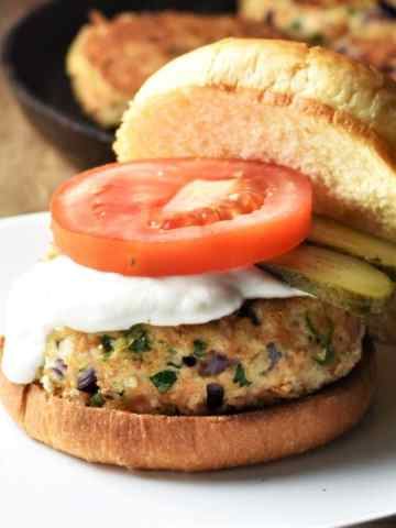 Chicken burger in open bun with sauce, slice of tomato and pickles.
