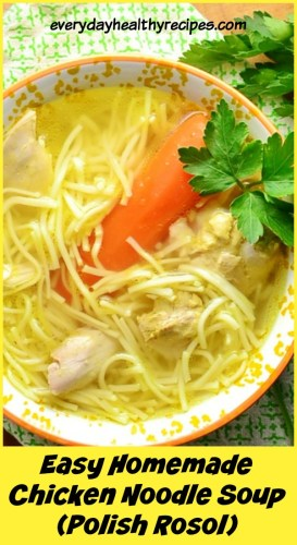 Chicken noodle rosol soup in orange bowl with parsley on green cloth.
