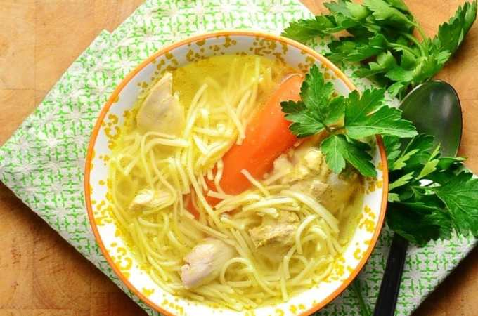 Chicken noodle rosol soup in orange bowl with spoon and parsley on green cloth.