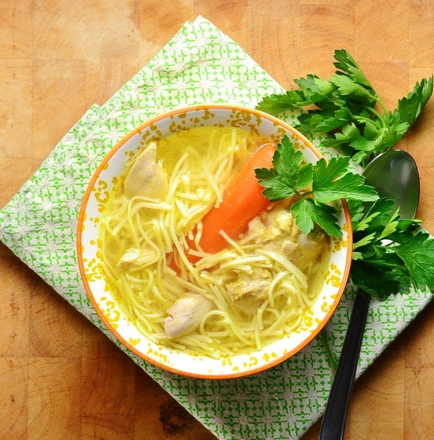 Chicken noodle soup in orange bowl with spoon and parsley on green cloth.