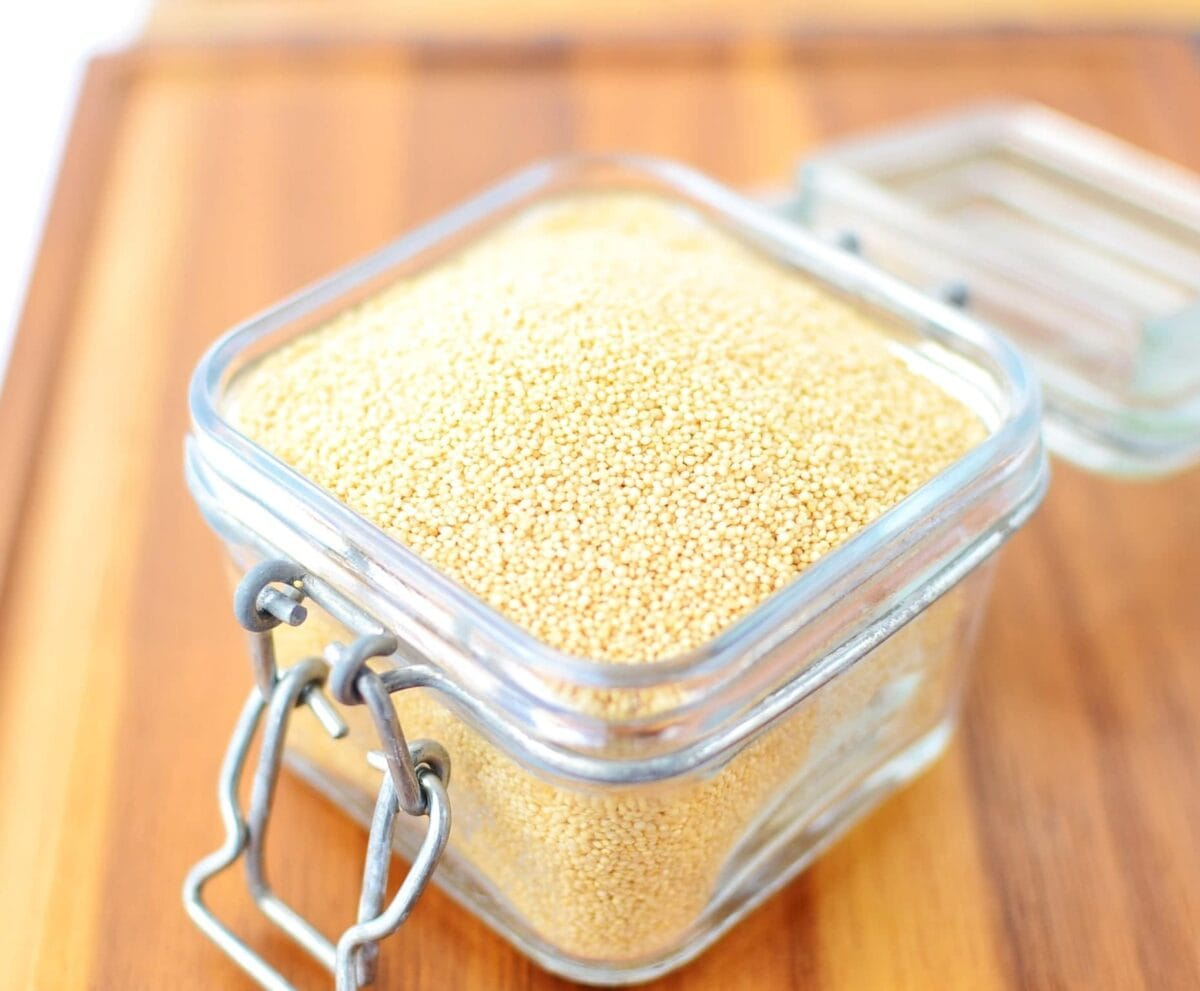 Raw amaranth seeds in open jar.