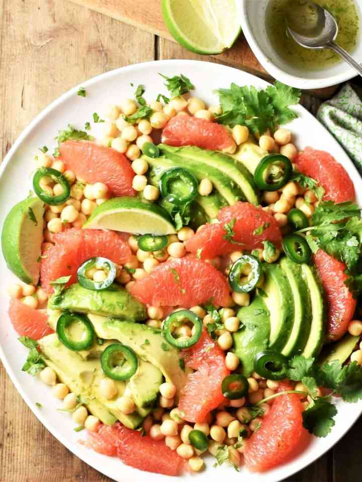 Grapefruit, avocado and chickpea salad on large plate with dressing in top right corner.
