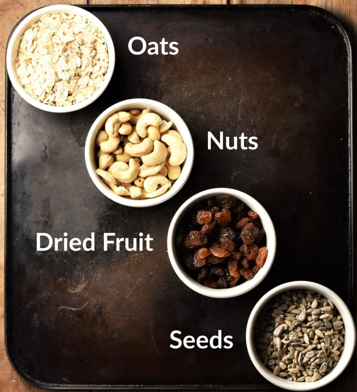 Top down view of oats, cashews, raisins and sunflower seeds in individual dishes.