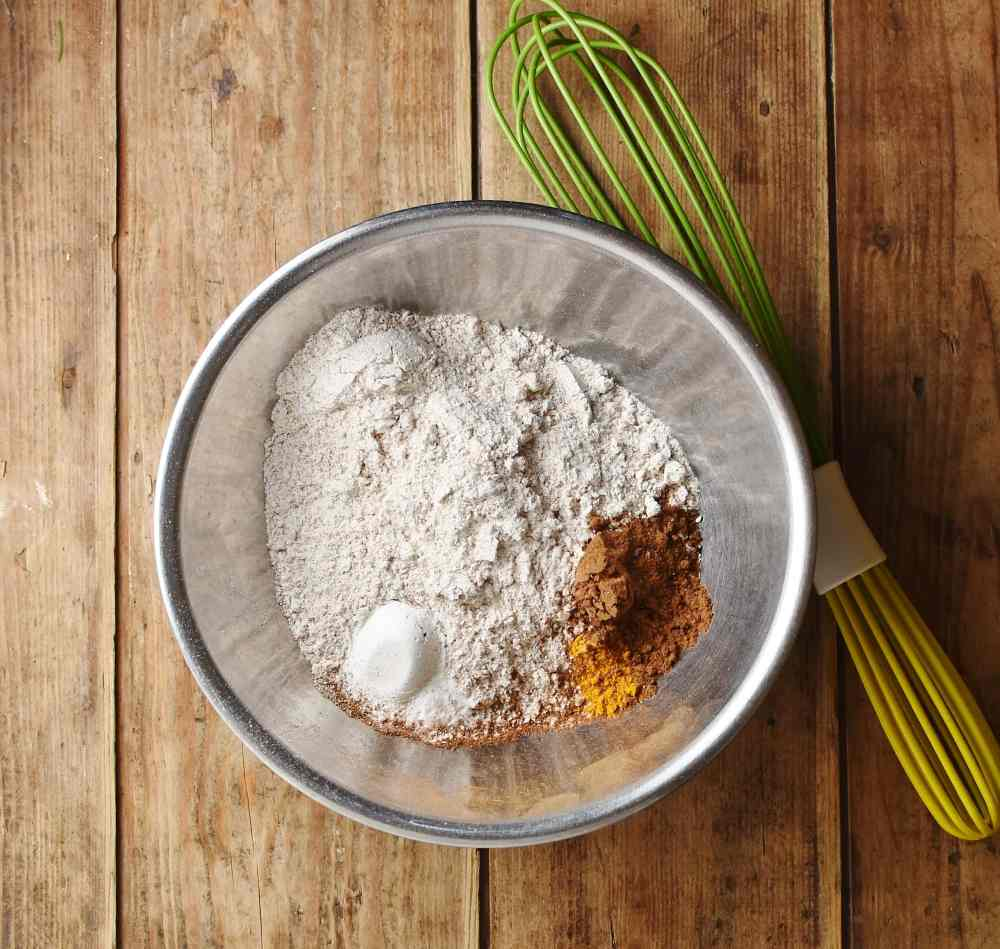 Flour and spices in metal bowl with green whisk.