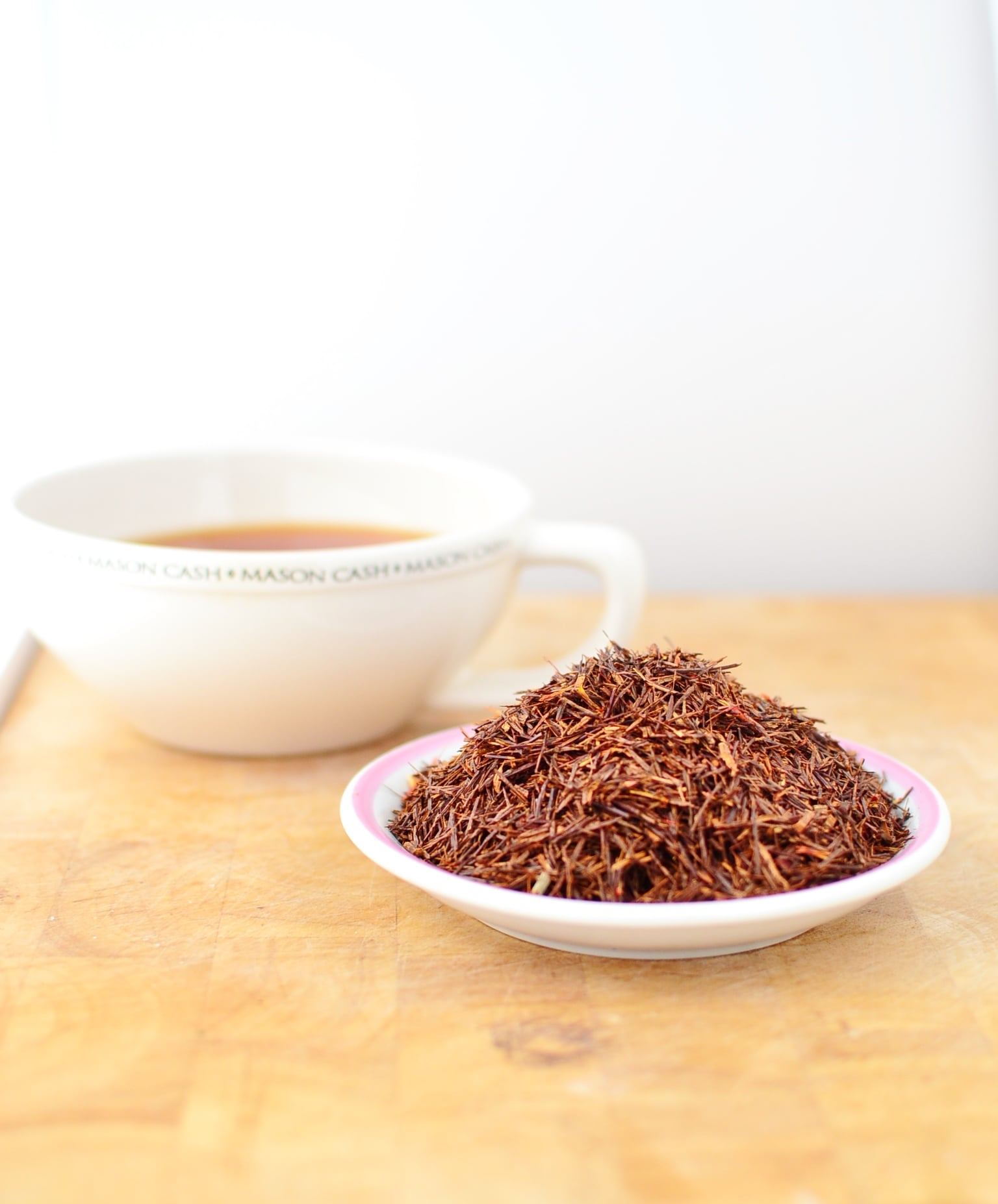 Rooibos leaves on top of small white plate, with rooibos tea in white cup in background.