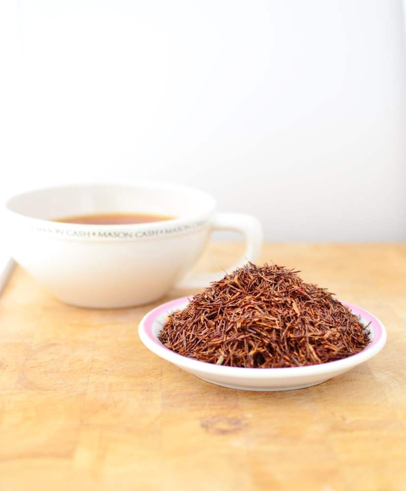 Side view of dried rooibos leaves on top of small plate, with rooibos tea in white cup in background.