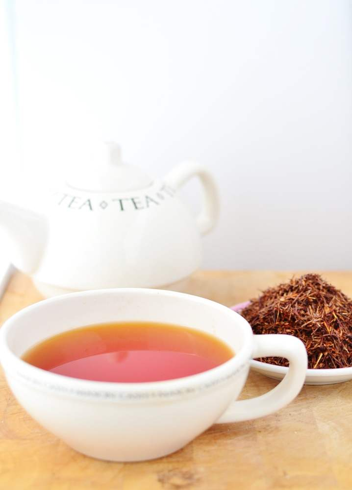 Rooibos tea in white cup, with rooibos leaves on top of white plate and white tea kettle in background.
