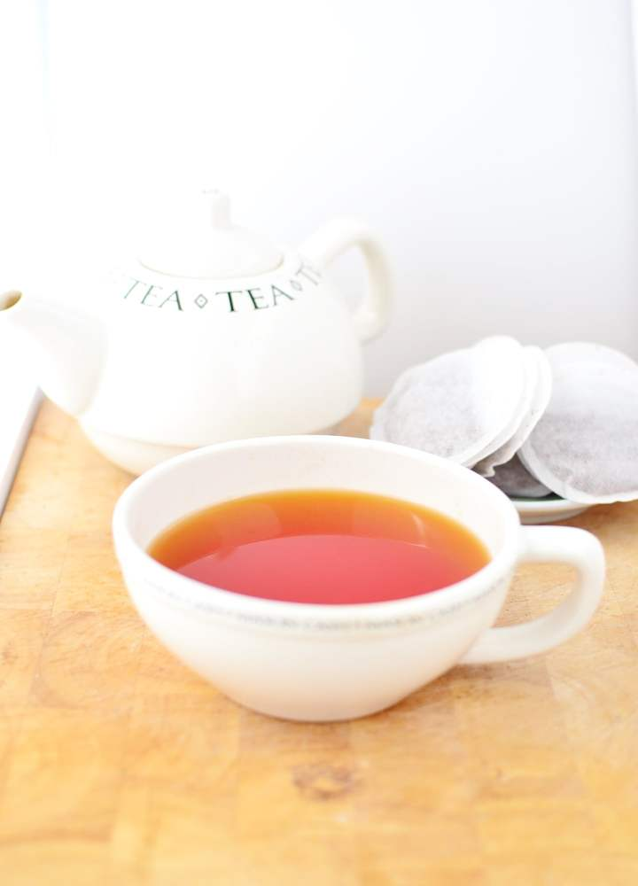 Rooibos tea in white cup, with tea bags and tea kettle in background.