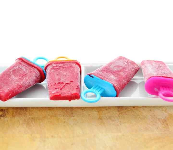 Rooibos raspberry ice lollies on top of white long dish, on wooden table.