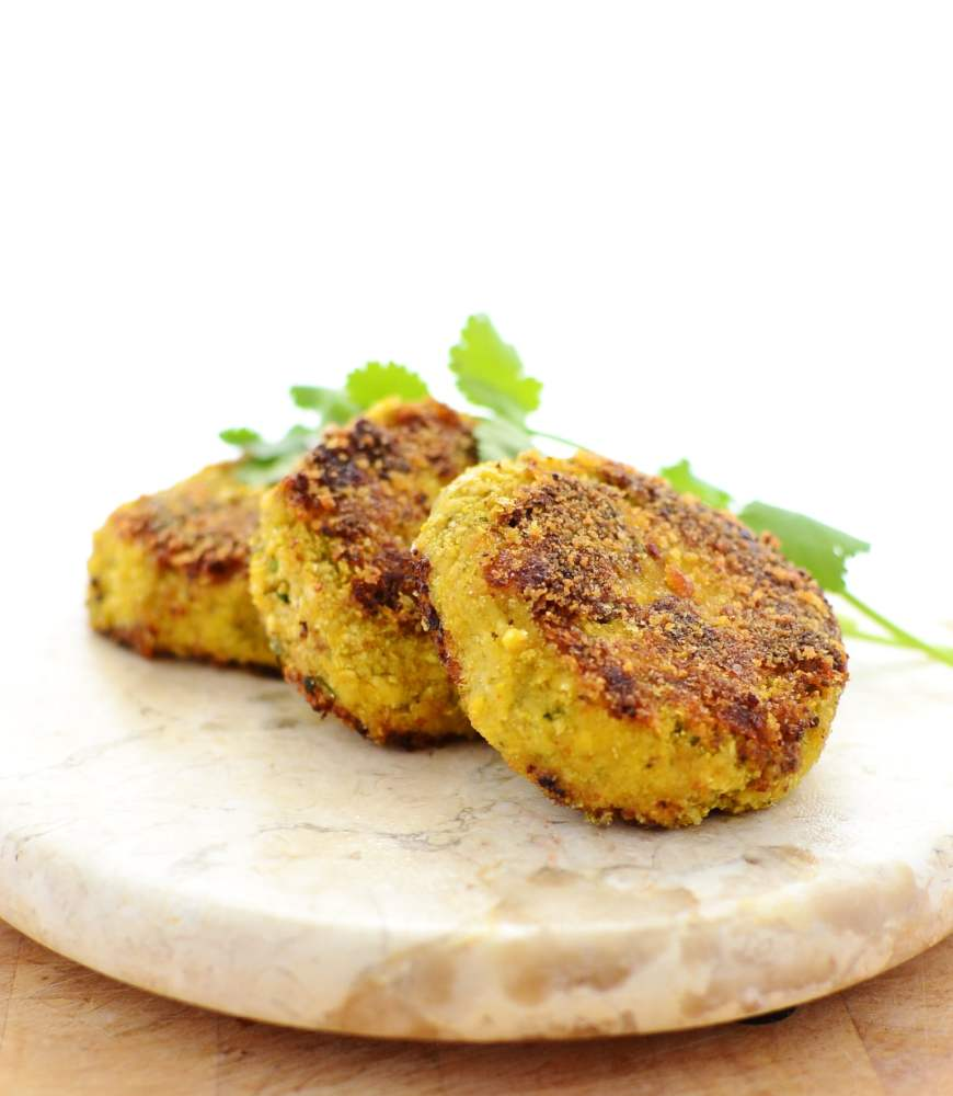 3 cauliflower patties with cheese on round marble plate and white background.