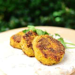 Cauliflower rice patties on marble plate with bushes in background.