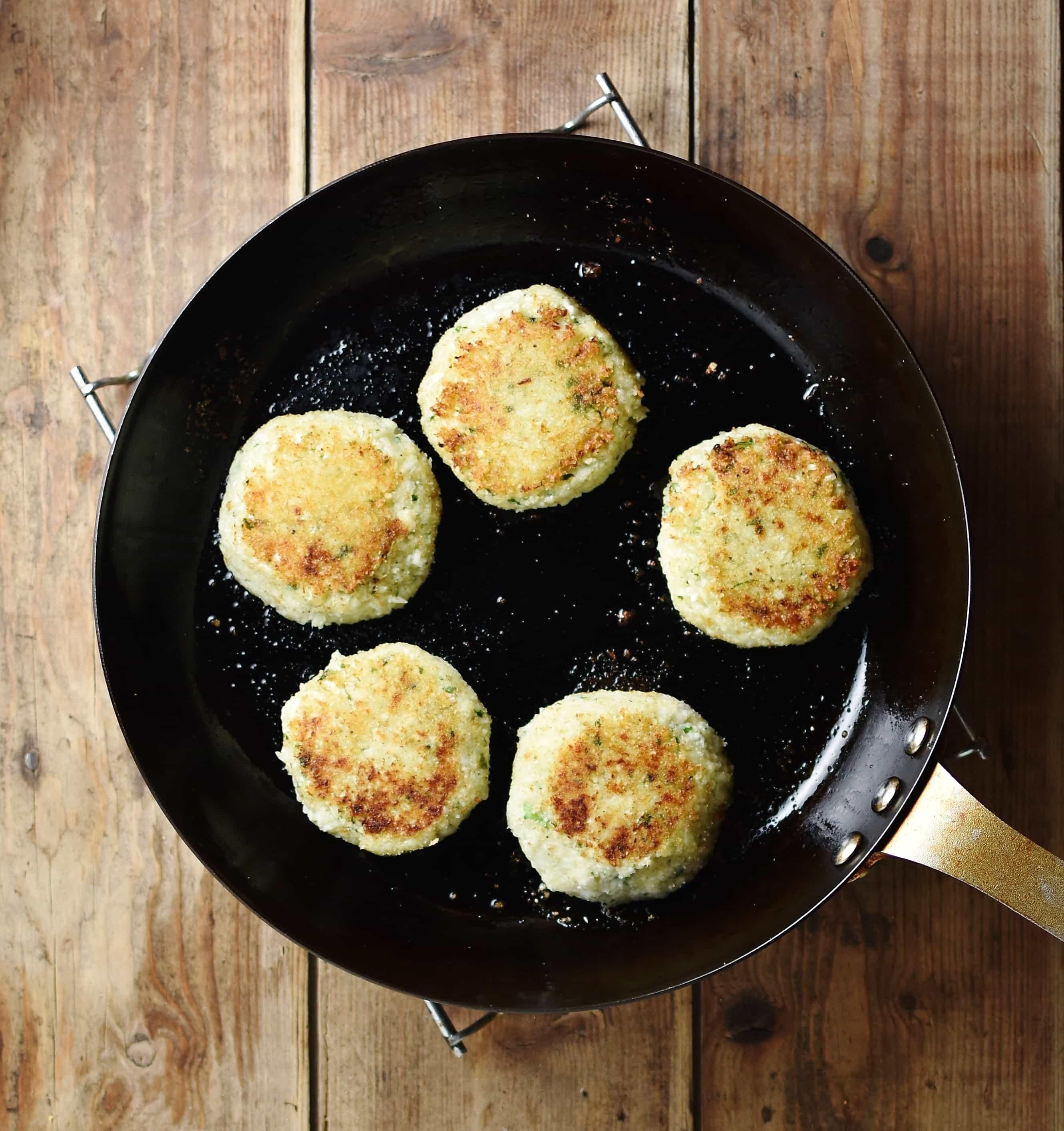 5 fried breaded patties in small pan.