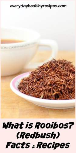 Dried rooibos tea leaves on top of small white plate, with rooibos tea in white cup in background.