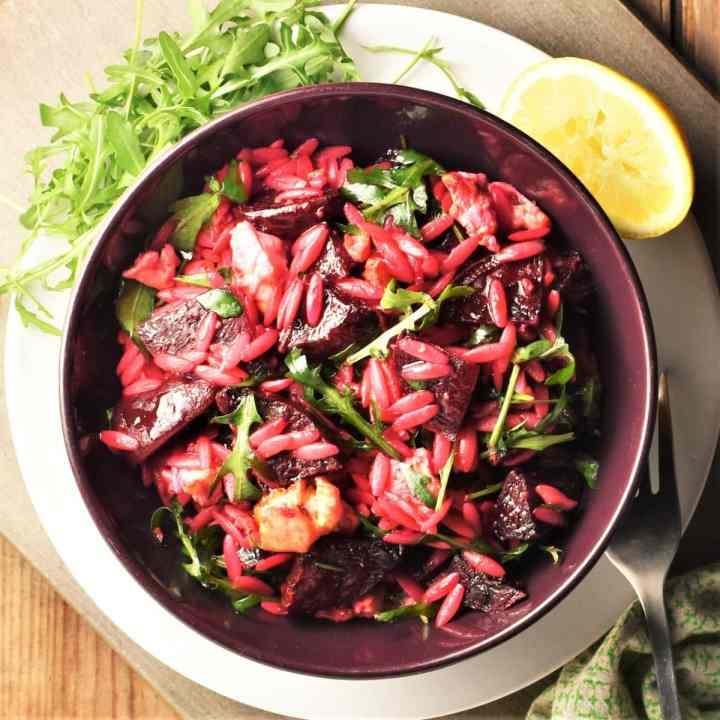 Top down view of beetroot and feta salad in purple bowl.
