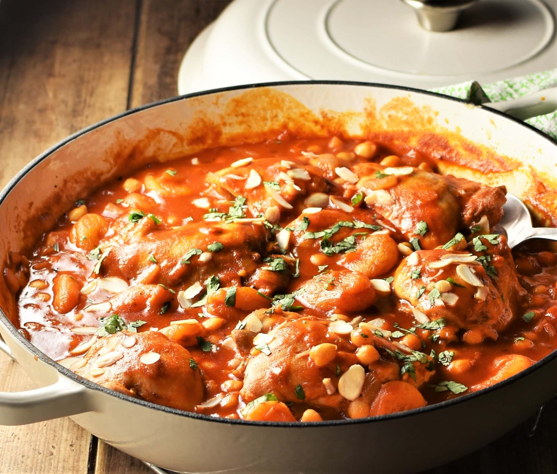 Side view of chicken thighs in tomato sauce with chickpeas in large shallow dish with lid in background.