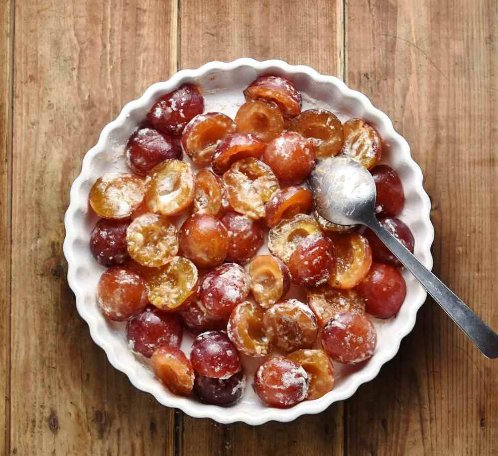 Halved plums with spoon inside white pie dish.