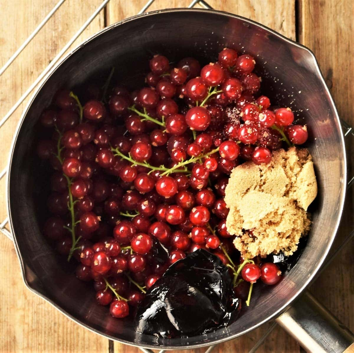 Redcurrants with stems, brown sugar and jelly in saucepan.