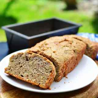 Banana bread with 1 slice on white plate on top of wooden board with bread tin in background.