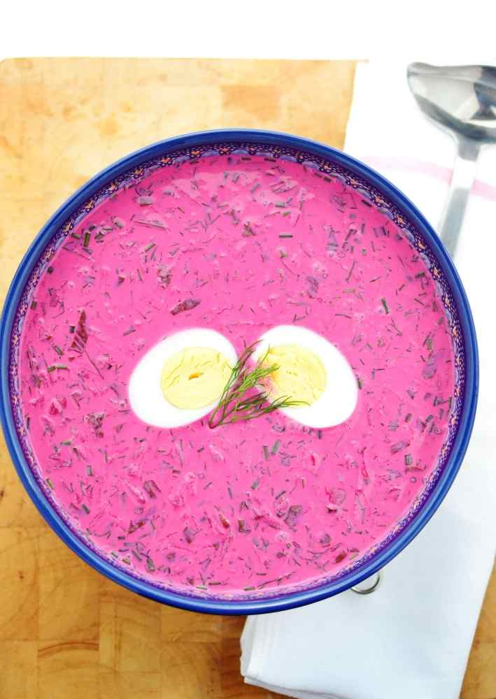 Top down view of cold beet soup with hard boiled egg halves in blue bowl with ladle on white cloth on top of wooden board.