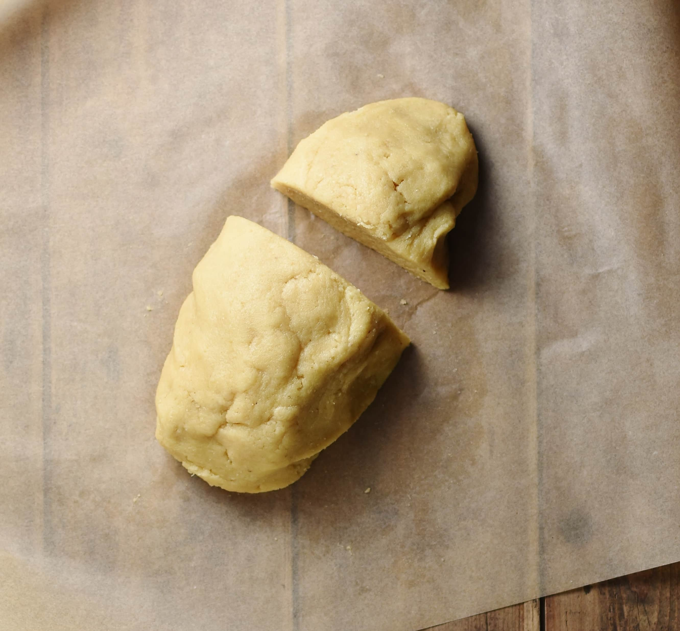 Cake dough divided into 2 parts on top of parchment paper.