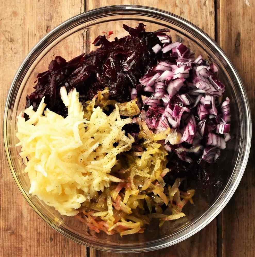Grated beet, apple, dill pickle and chopped red onion in mixing bowl.