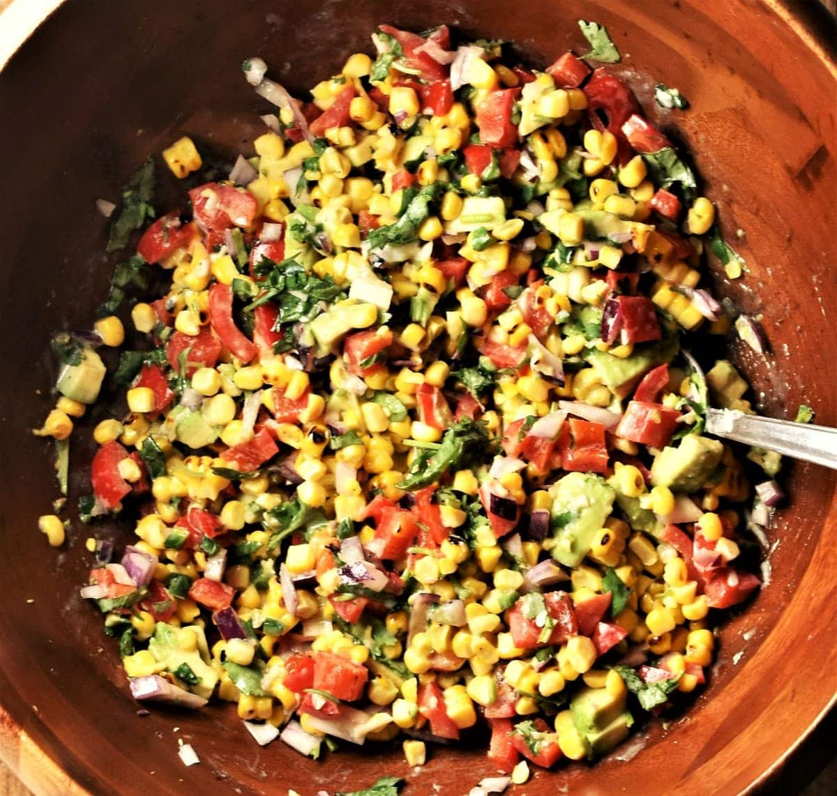 Corn and vegetable salsa in large wooden bowl with spoon.