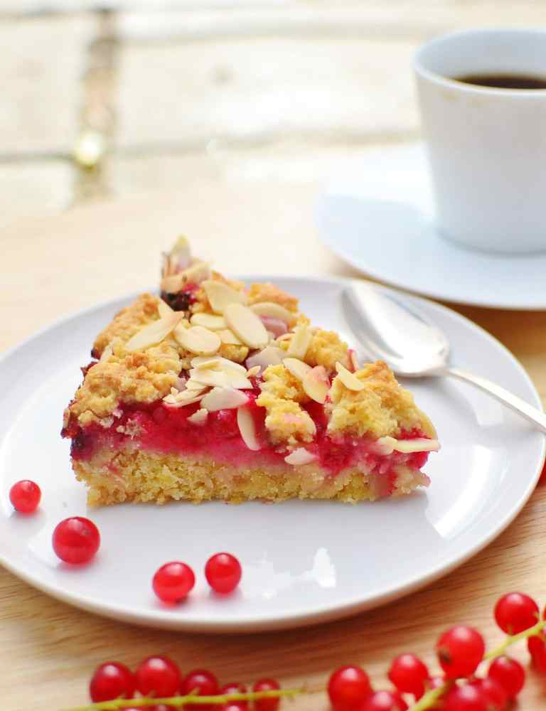 Side view of almond redcurrant cake slice on white plate with redcurrants on wooden surface with white cup and saucer in background.