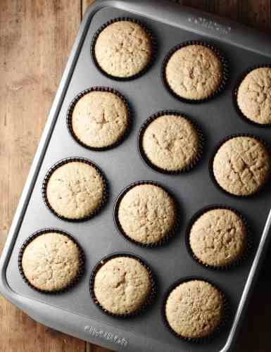 Cupcakes in brown cases in muffin pan.