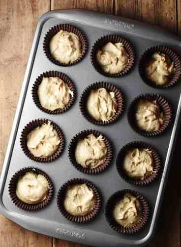 Cupcake batter in 12 brown liners in muffin pan.