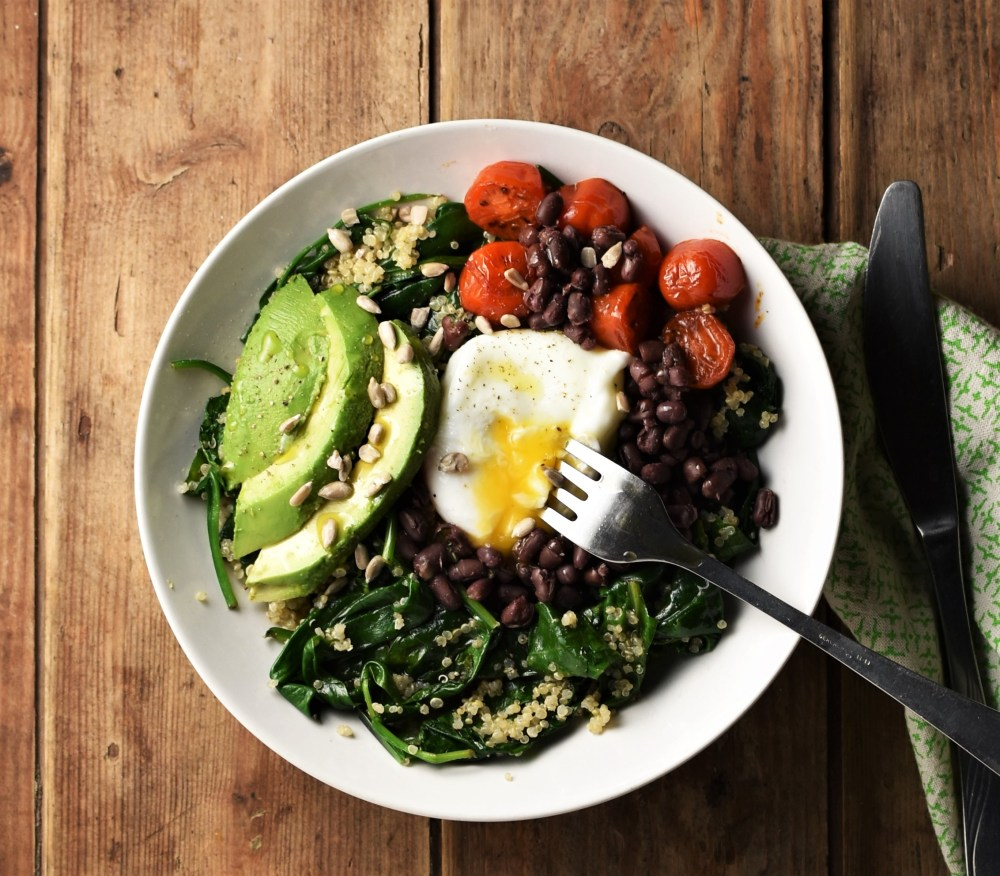 Spinach with quinoa mixture topped with sliced avocado, poached egg, beans and small tomatoes in white bowl with fork and green cloth with knife to the right.