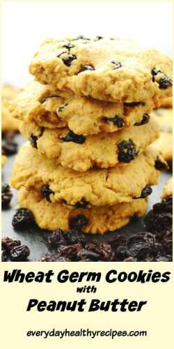 Raisin cookies stacked on top of dark surface surrounded by raisins.