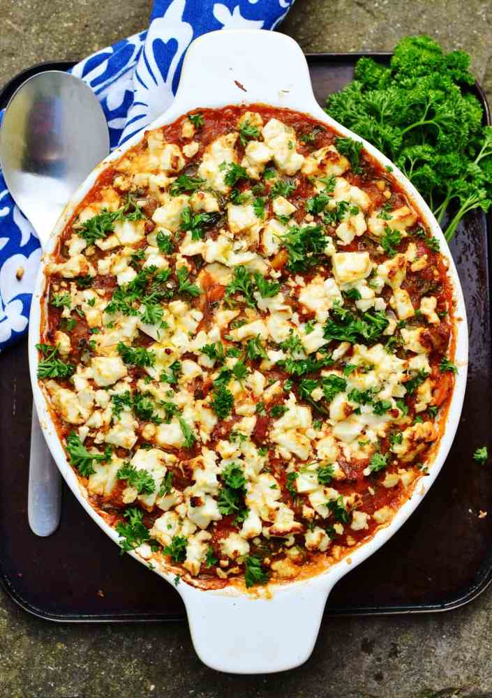 Easy tuna bake in white oval casserole fish, spoon, white-and-blue cloth, parsley on dark oven tray.