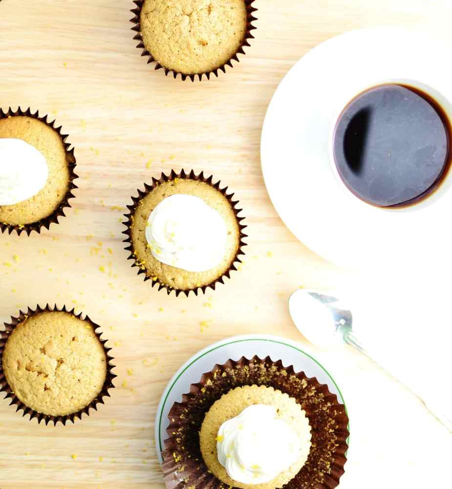 Top down view of cupcakes with white frosting and cup of coffee on white saucer.