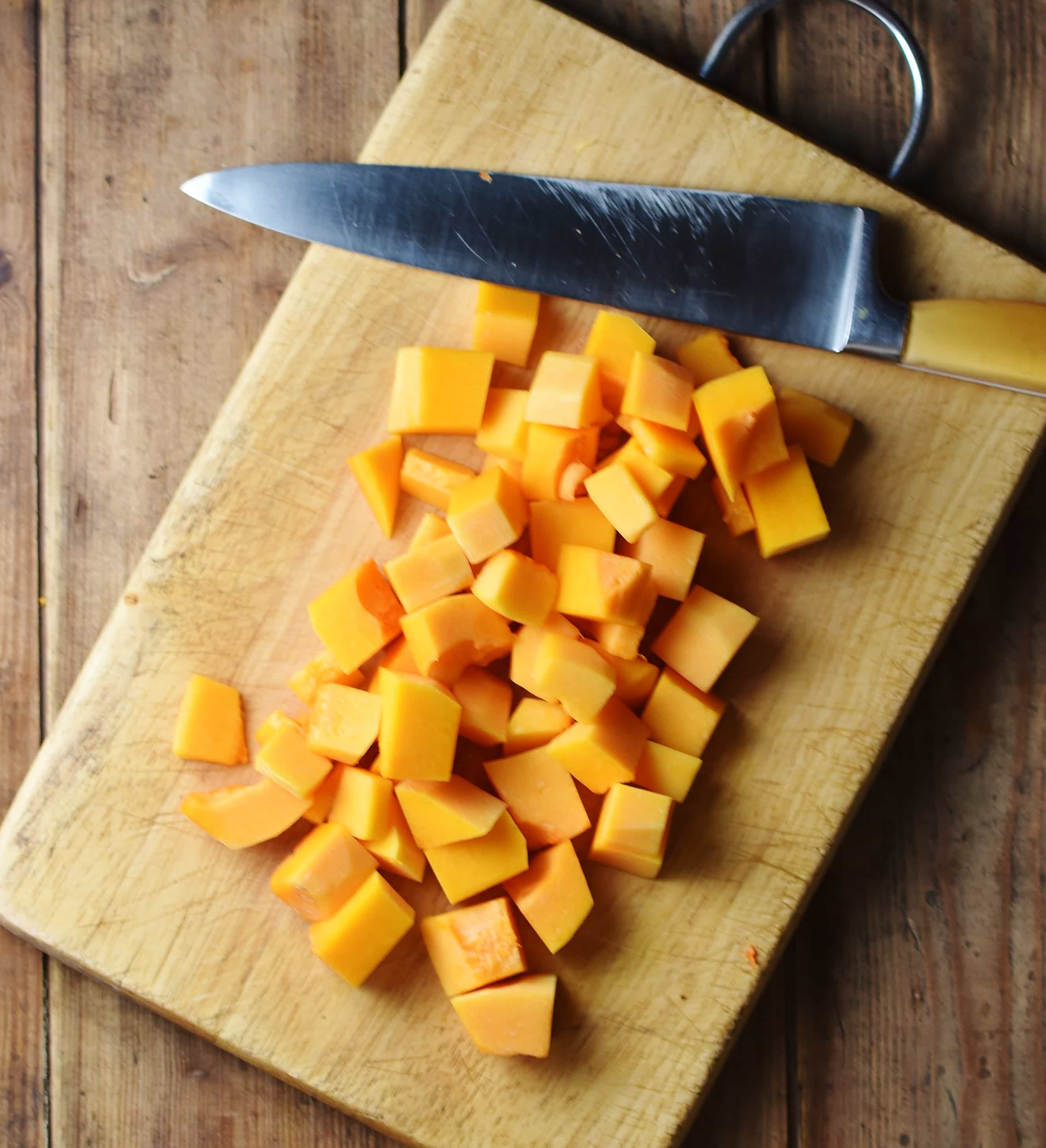 Peeled and cubed butternut squash on top of cutting board with knife.