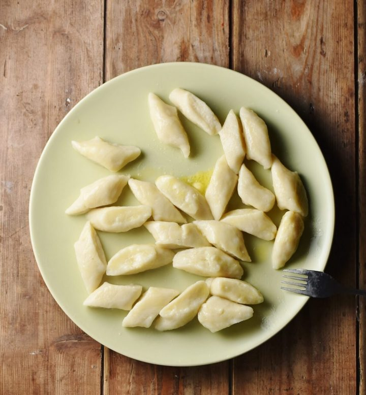 Boiled Polish potato dumplings on top of yellow plate with fork.