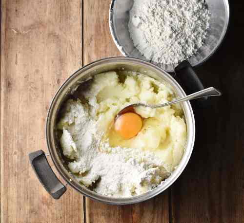 Mashed potatoes with egg and flour in pot with spoon and flour in metal bowl in top right.