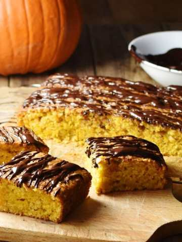 Pumpkin cake slices with chocolate drizzle and more cake in background, with pumpkin and melted chocolate in white bowl in top right.