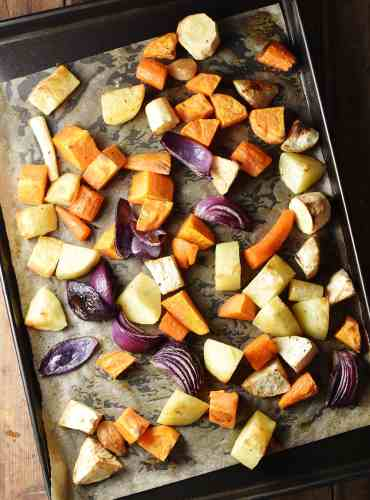 Roasted chunks of root vegetables and red onion on baking sheet lined with paper.