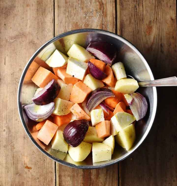 Chunks of peeled root vegetables and red onion.