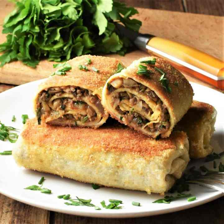 Side view of fried crepes with mushrooms on top of plate with herbs in background.
