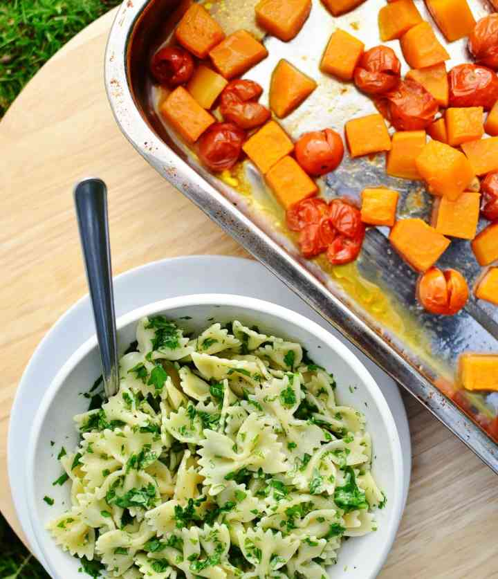 Top down view of pasta with arugula and spoon in white bowl on top of white plate and roasting tin with chunks of squash and tomatoes.