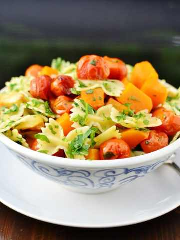Pasta with butternut squash, cherry tomatoes and herbs in white bowl with blue pattern, on top of white plate.