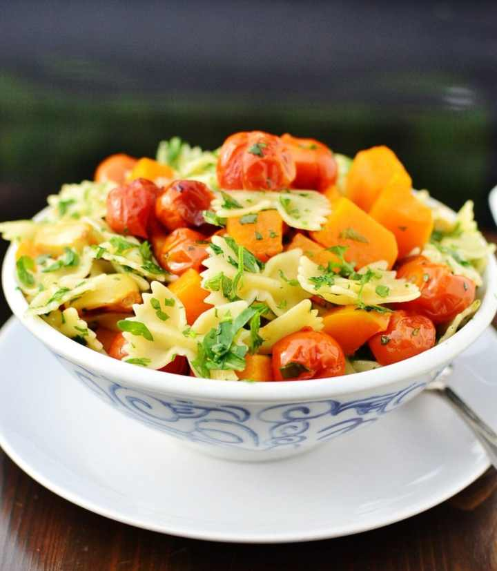Bow tie pasta with butternut squash pieces, roasted cherry tomatoes and herbs inside white bowl with blue pattern on top of white plate.