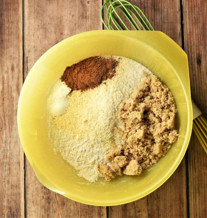 Flour, sugar and spices in large yellow bowl with green whisk to the right.
