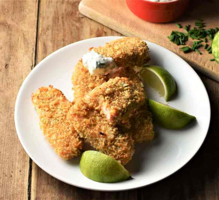 Breaded fish fingers on top of plate with lime wedges.