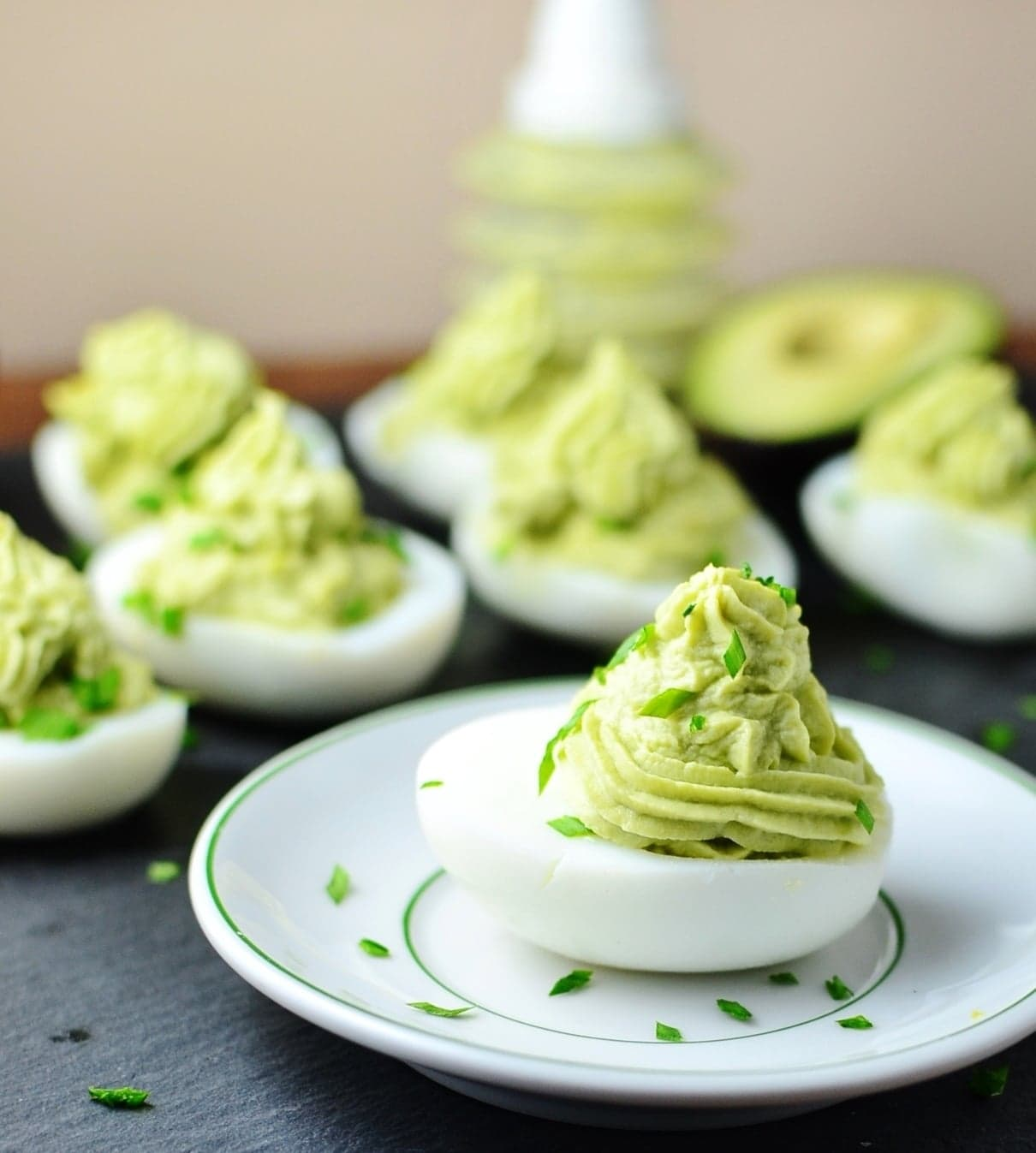 Deviled eggs with avocado on small white plate with garnish of chives and deviled eggs in background.