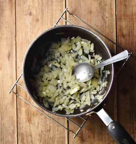 Chopped onion and spoon inside large pot on top of cooling rack.
