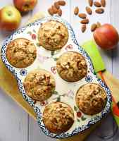Top down view of muffins with almond flakes on top inside 6-hole ceramic muffin pan on top of cutting board, with green spatula, almonds and apples in background.