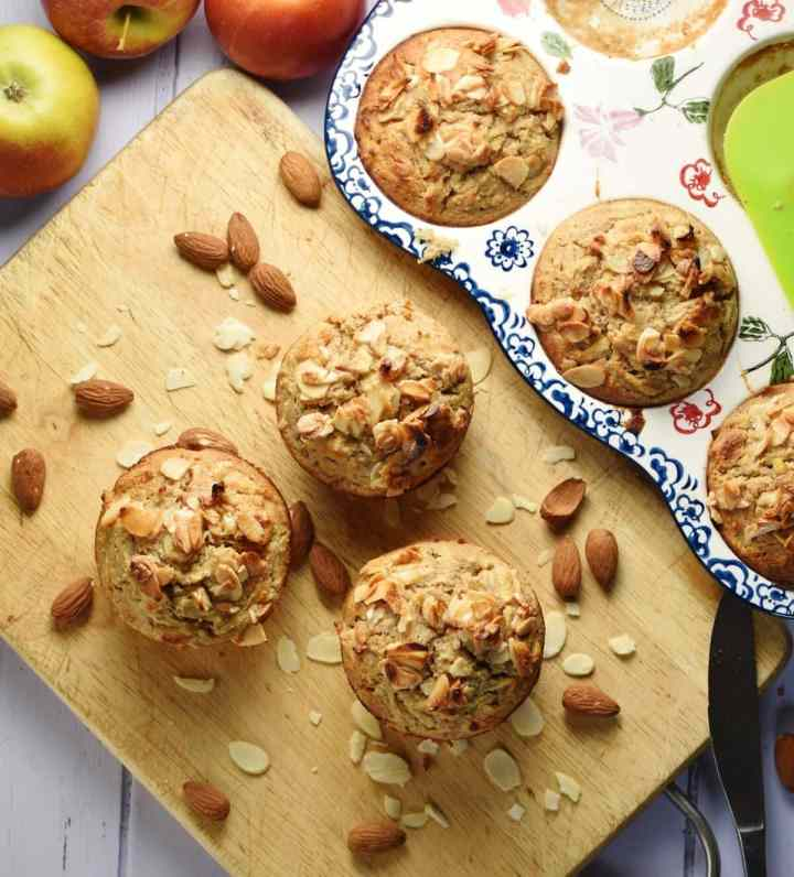 Muffins with almond flakes and almonds on top of wooden board, and muffins in ceramic pan in background.